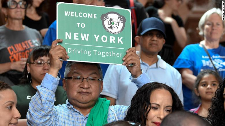 FILE - In this June 17, 2019 file photo, a protester holds a sign as members of the state Assembly speak in favor of legislation of the Green Light Bill, granting undocumented immigrant driver's licenses during a rally at the state Capitol, in Albany, N.Y. The bill passed making New York the 13th state to authorize licenses for drivers without legal immigration status. On Monday, Dec. 16 license applicants without a valid Social Security number will be able to apply for a driver's license. An estimated 265,000 immigrants without legal documents are expected to get driver's licenses within three years, more than half of them in New York City, according to the Fiscal Policy Institute.(AP Photo/Hans Pennink, File)