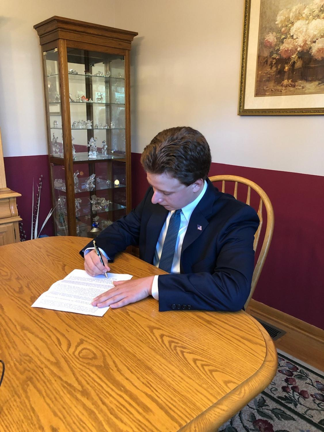 Senior Student, Nick Mattei Stamps his Signature on own Letter to Send to Representatives